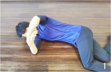 斜め下向きで寝て左足を交差するように前に置いておきます。 左手で右手首を持ちます。 左手で右手首をゆっくり上から地面に向かって押します。 伸びるのを感じるところでしばらくキープします。