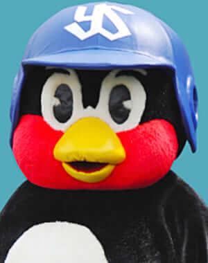 つば九郎が初登場したのは1994年4月9日の阪神タイガース戦です。2008年にはプロ野球のマスコットとして初の開催試合連続1000試合出場を達成しました。つば九郎はその名の通り、ツバメをモチーフにしたマスコットキャラクターです。  名前は  ツバメの古称「つばくろ」 つばぜりあいに強く、苦労しながら接戦に勝利する この2つに由来しています。  プロ野球のマスコットキャラクターは大体ユニフォームを着用しています。  しかし、つば九郎だけはユニフォームを着用しない裸キャラです。裸にネクタイ=正装という服装の時点で独自路線を走っています。